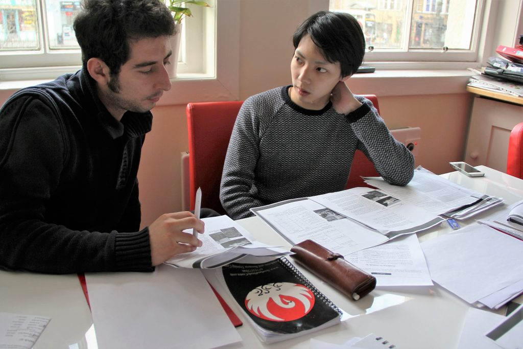 Image of two people talking at a table filled with school papers and books.